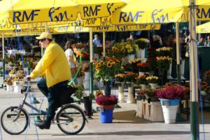 Man riding bicycle on a flower shop